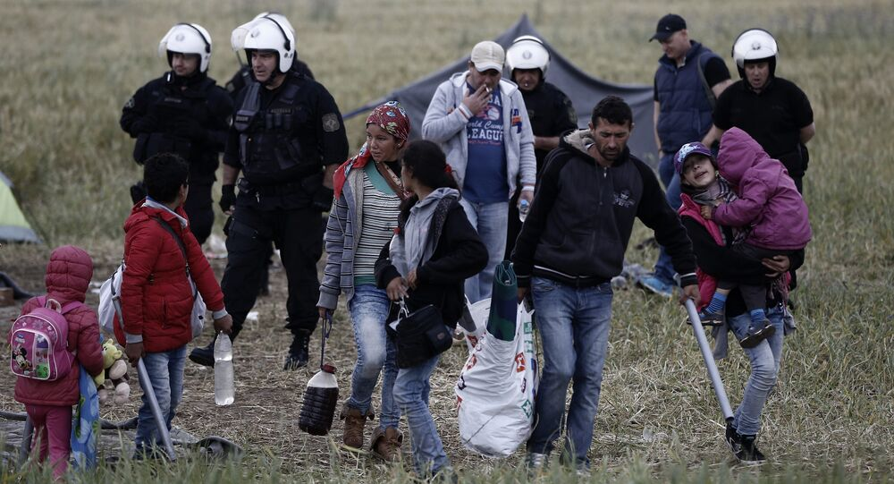 A migrant family carries their belongings during an evacuation operation by police forces of a makeshift migrant camp at the border at the Greek-Macedonian border near the village of Idomeni, on May 24, 2016