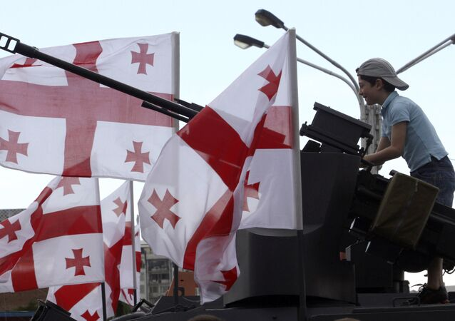 A Georgian boy plays atop an armored vehicle put on display with other Georgian military machinery to mark Independence Day in Tbilisi, Georgia, Saturday, May 26, 2012