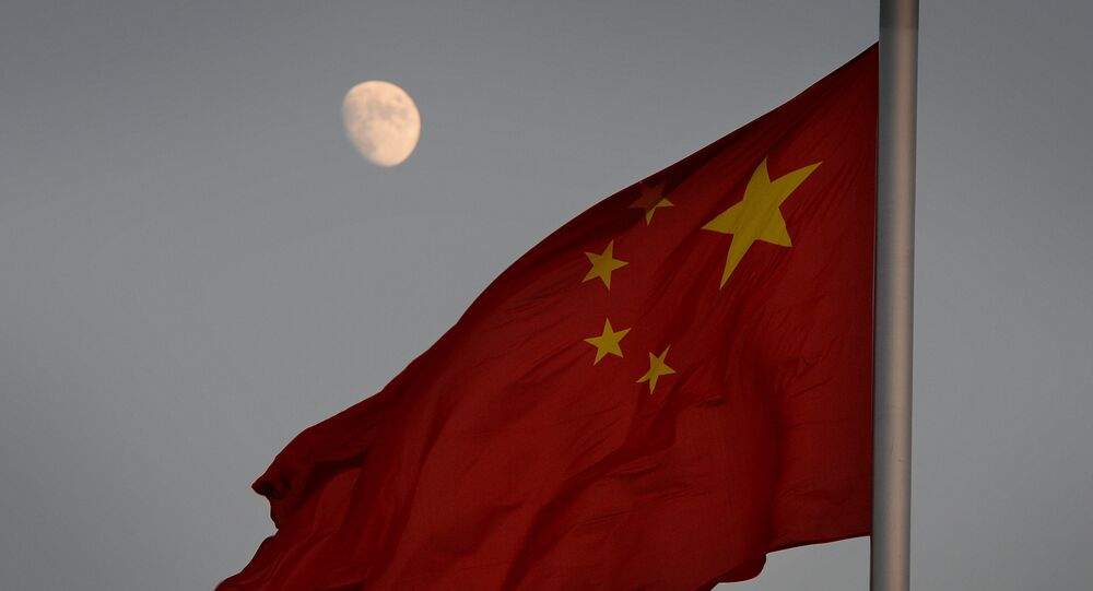 The Chinese flag is seen in front of a view of the moon at Tiananmen Square in Beijing on December 13, 2013