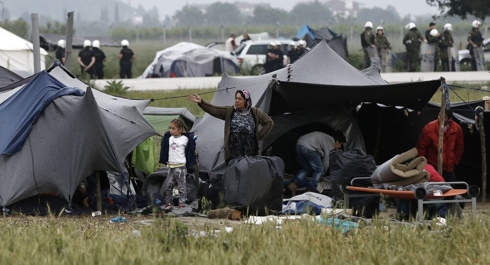 A migrant family stands outside their tent during an evacuation operation by police forces of a makeshift migrant camp at the border at the Greek-Macedonian border near the village of Idomeni, on May 24, 2016