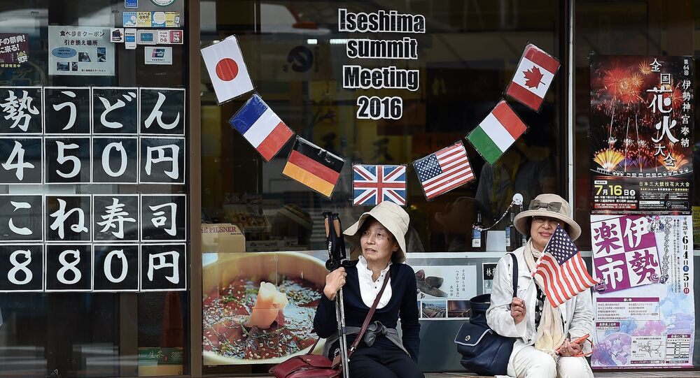 Elderly Japanese women sit under a welcome message outside a shop during the world leaders' visit to the Ise-Jingu Shrine in the city of Ise, Mie prefecture on May 26, 2016 on the first day of the G7 leaders summit