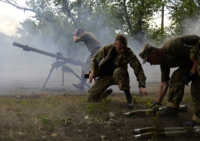 Ukrainian servicemen shout from SPG-9 antitank grenade launcher during the combat with the pro-Russian separatists near Avdeevka, Donetsk region, on June 18, 2015