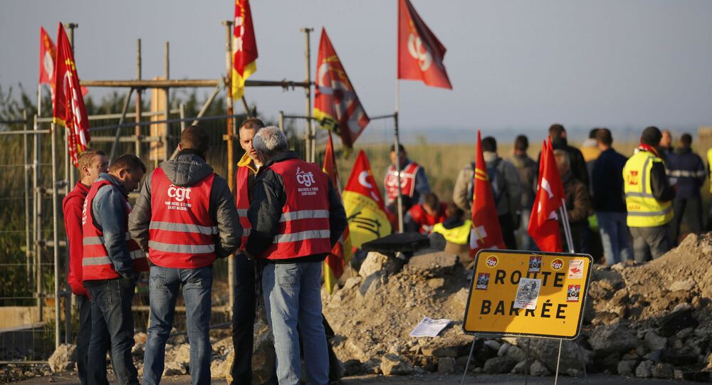 Striking French labour union employees stand near a barricade to block the entrance of the depot of the SFDM company near the oil refinery to protest the labour reforms law propal, in Donges, France, May 26, 2016.