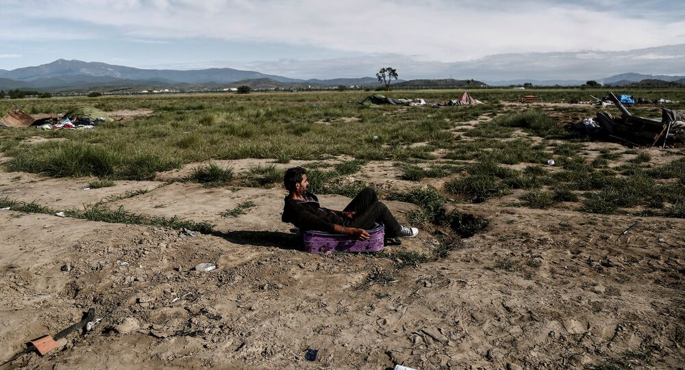 Syrian Kurd Nidal Daud, 37, sits on a suitcase as he waits to be transferred to a hospitality centre during a police operation at a refugee camp at the border between Greece and Macedonia, near the village of Idomeni, Greece, May 25, 2016