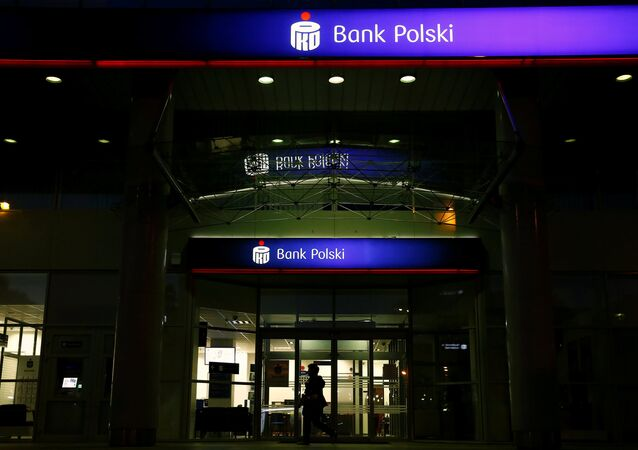 A woman walks outside an entrance to the PKO BP bank headquarters, Poland's largest lender, in Warsaw, Poland May 6, 2016