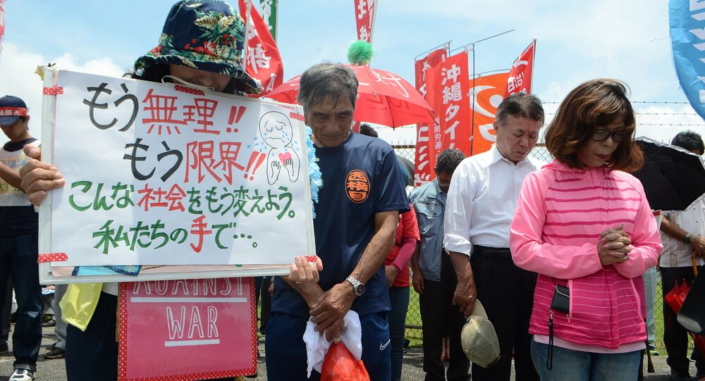 People offer a silent prayer in front of the US Kadena Air Base in Cyatan, Okinawa prefecture, to protest against the US military presence in Okinawa on May 21, 2016