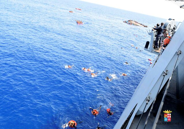 Migrants from a capsized boat are rescued during a rescue operation by Italian navy ships Bettica and Bergamini off the coast of Libya in this handout picture released by the Italian Marina Militare on May 25, 2016