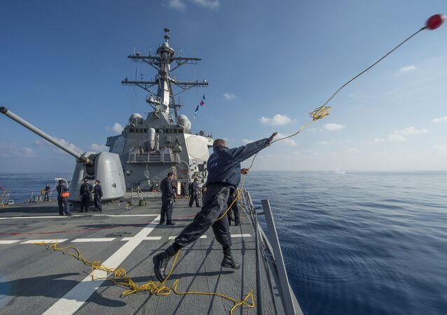 Boatswain's Mate 3rd Class Dontrell Dorsett, from Fort Worth, Texas, heaves a line over the side of USS Cole (DDG 67) during a man overboard drill (File)