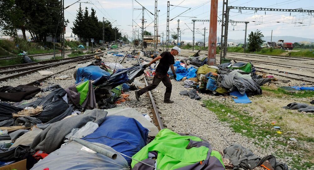 A worker removes tents used by migrants during a police operation to evacuate a migrants' makeshift camp at the Greek-Macedonian border near the village of Idomeni, Greece, May 26, 2016