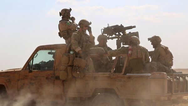 Armed men in uniform identified by Syrian Democratic forces as US special operations forces ride in the back of a pickup truck in the village of Fatisah in the northern Syrian province of Raqa on May 25, 2016 - Sputnik International