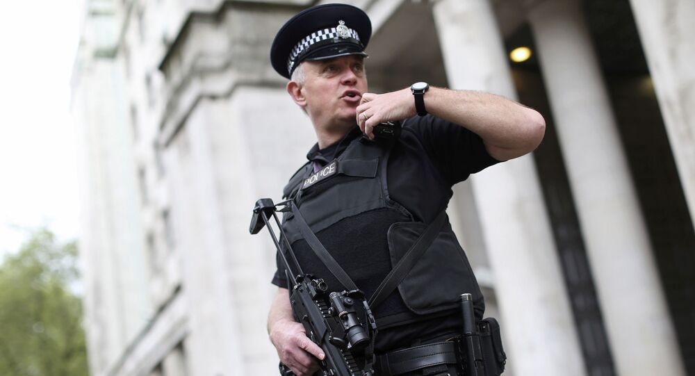 An armed police officer speaks on his radio as he patrols near the Ministry of Defence in London, Britain May 11, 2016
