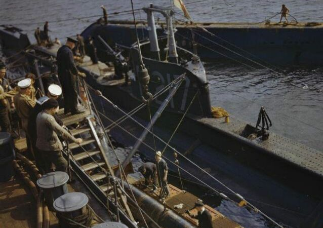 The depot ship HMS FORTH transferring a practice torpedo to the submarine P311