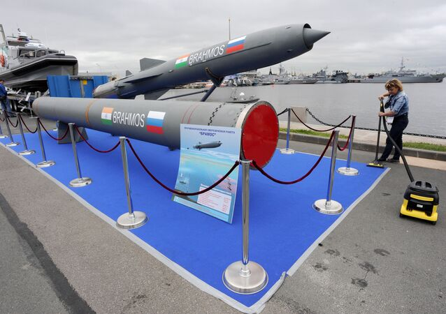 A woman cleans a carpet flooring close to a Brahmos supersonic cruise missile at the International Maritime Defence Show in St. Petersburg.