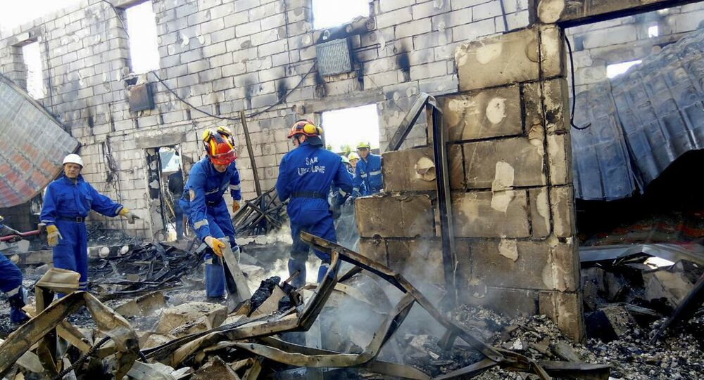 Rescuers inspect the debris of a residential house after a fire broke out, in the village of Litochky, northeast of Kiev, Ukraine, May 29, 2016.