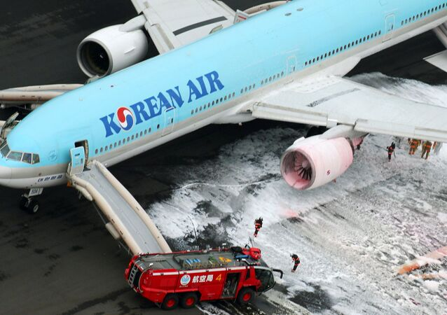 An aerial picture shows fire fighters spraying foam at the engine of a Korean Air Lines plane after smoke rose from it at Haneda airport in Tokyo, Japan, May 27, 2016