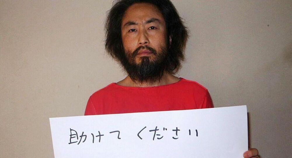 This undated picture provided by Japan's Jiji Press news agency, taken at an undisclosed location, on May 30, 2016 shows Japanese freelance journalist Jumpei Yasuda holding a piece of paper with a handwritten message in Japanese. The fresh photo, which received widespread coverage in Japanese media on May 30, 2016, shows Yasuda, who has been missing for almost a year, wearing an orange shirt, his hair and beard grown long.