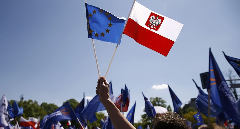 People wave EU and Polish flags as they march during anti-government demonstration organized by main opposition parties in Warsaw, Poland May 7, 2016.