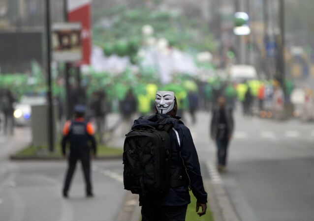 A man watches as protesters begin to march during a demonstration against proposed working regulations in Brussels on Tuesday, May 31, 2016.