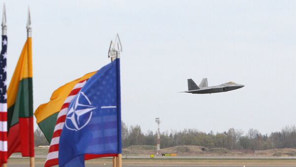 A US Air Force F-22 Raptor fighter aircraft flies at the Air Base of the Lithuanian Armed Forces in Šiauliai, Lithuania, on April 27, 2016 behind flags of US, Lithiania and the NATO - Sputnik International