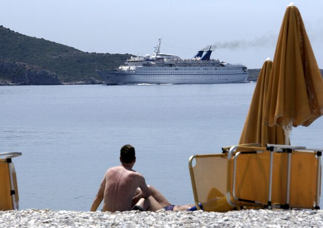 A vacationer at the island of Samos looks at the ferry Orient Queen passing along the coast