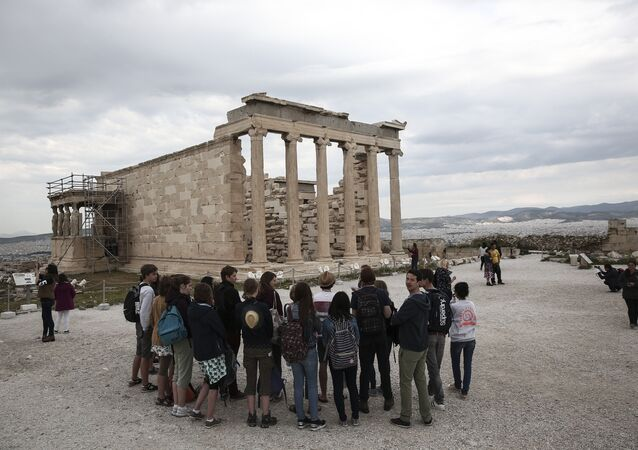 Tourists listen to a guide as they stand in front of the Erechtheion temple during a visit at the Acropolis hill in Athens, on Wednesday, April 15, 2015
