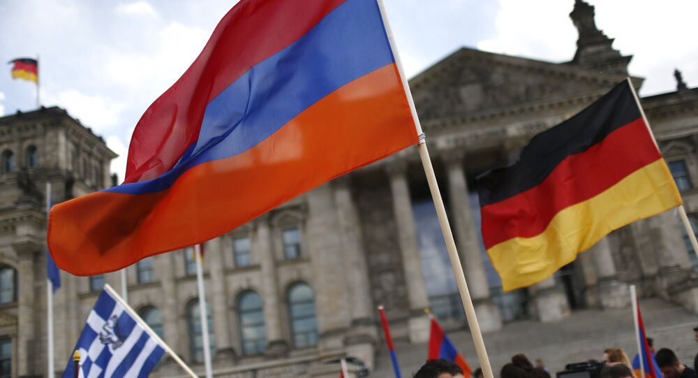 Supporters wave Armenian and German flags in front of the Reichstag, the seat of the lower house of parliament Bundestag in Berlin, Germany, June 2, 2016, as they protest in favour of approval of a symbolic resolution by Germany's parliament that declares the 1915 massacre of Armenians by Ottoman forces a genocide