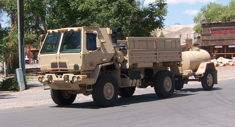 An armored LMTV (Light Medium Tactical Vehicle) pulls a water buffalo through Beatty, Nevada.