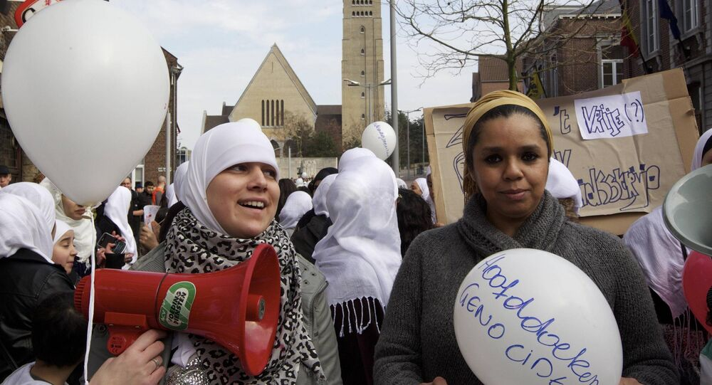 Muslim women with white hijaabs (the head scraf traditionally worn by Muslim women) protest against an employee of the Dutch department store chain HEMA in Genk being fired for wearing a headscarf, on March 12, 2011