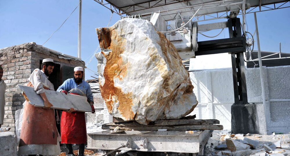 Afghan labourers work at a marble stone factory on the outskirts of Jalalabad on March 12, 2013