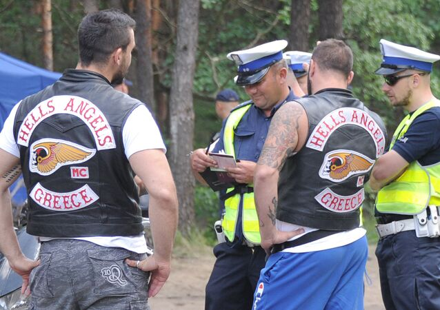 Two Hells Angels bikers are checked by police officers as they wait to enter an enclosed holiday center near Warsaw, Poland, Friday, June 3, 2016