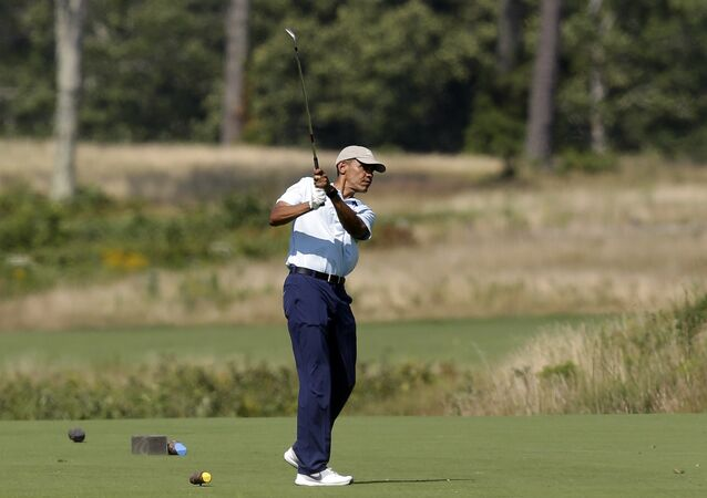 President Barack Obama watches the flight of his ball as he tees off while golfing at Vineyard Golf Club, in Edgartown, Mass