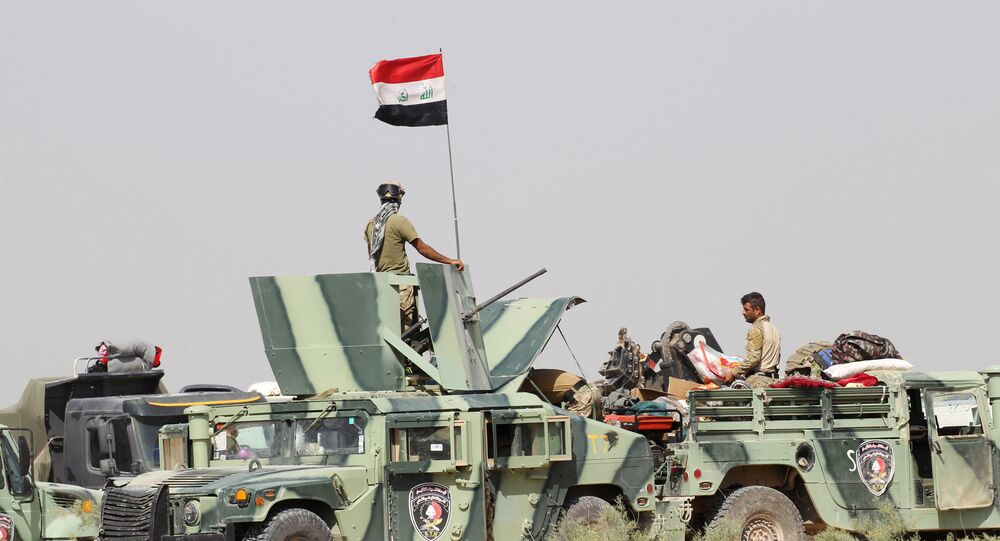 Iraqi security forces sit in military vehicles in the Nuaimiya suburb of Fallujah, Iraq