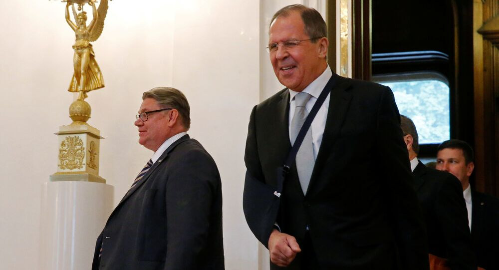 Russian Foreign Minister Sergei Lavrov (R) and his Finnish counterpart Timo Soini enter a hall during a meeting in Moscow, Russia
