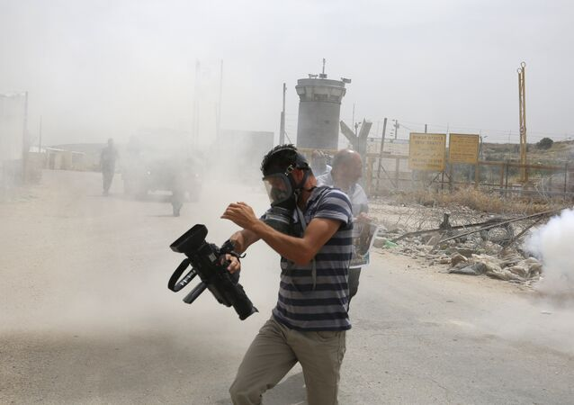 Palestinian journalists run for cover from tear gas canisters fired by Israeli forces during a demonstration in support of Palestinian journalists on the occasion of the World Press Freedom day outside the compound of the Israeli-run Ofer prison near Betunia in the occupied West Bank, on May 3, 2016