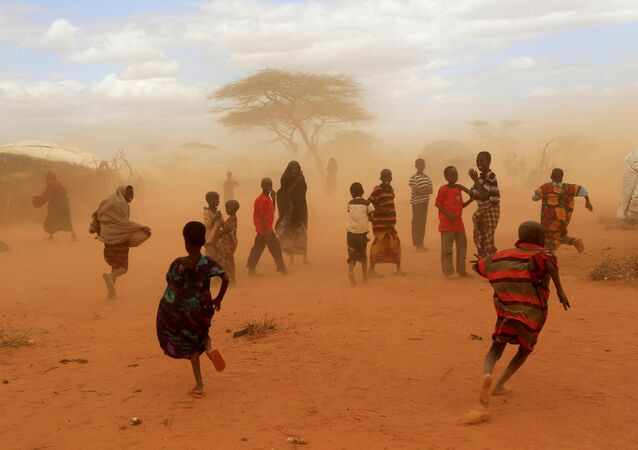 Newly-arrived refugees run away from a cloud of dust at the Dagahaley refugee camp in Dadaab, near Kenya's border with Somalia in Garissa County, Kenya, July 16, 2011.