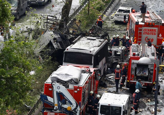 Forensic experts (L) and firefighters stand beside a Turkish police bus which was targeted in a bomb attack in a central Istanbul district, Turkey, June 7, 2016.
