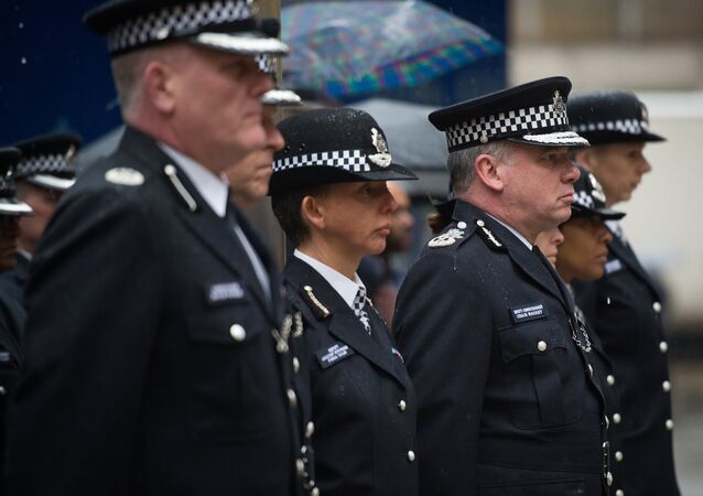 Deputy Commissioner of Britain's Metropolitan Police Craig Mackey (3rd R) leads police officers in a two minute silence outside Scotland Yard in London, on January 8, 2015.