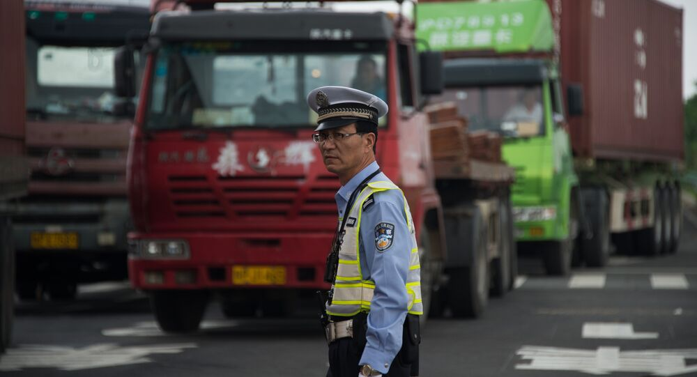 Policeman gestures in front of trucks, China