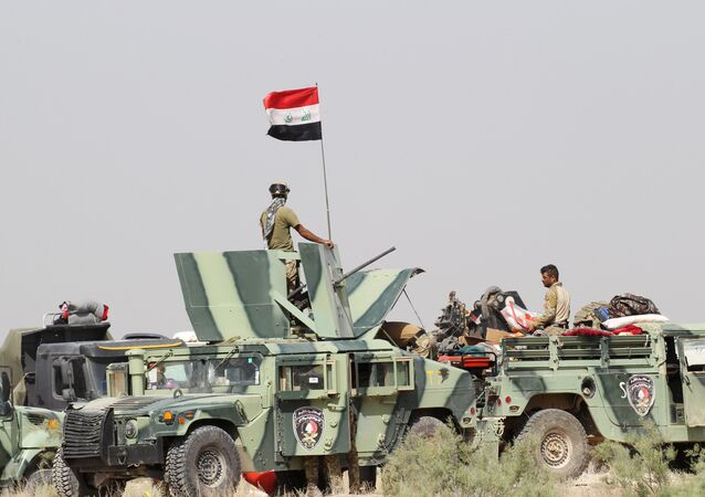 Iraqi security forces sit in military vehicles in suburb of Fallujah, Iraq