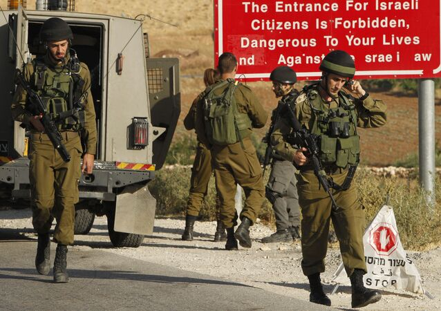 Israeli soldiers are seen at one of the entrances of the Palestinian village of Yatta in the occupied West Bank on June 9,2016 after the army entered the village in search for clues leading to an attack the previous night in the Israeli city of Tel Aviv in which four people were killed and 16 others wounded