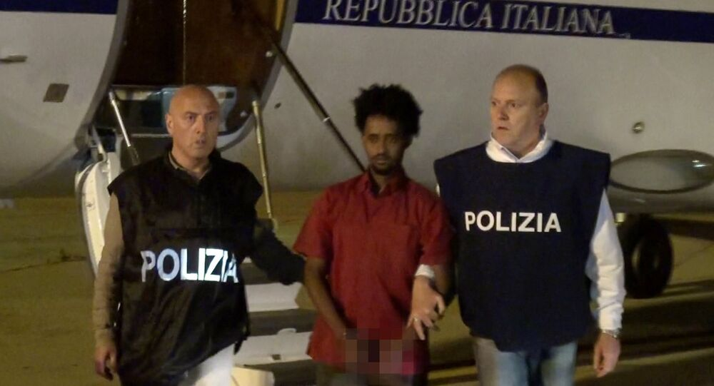 Medhanie Yehdego Mered (C), 35, is pictured with Italian policemen as they land at Palermo airport, Italy, following his arrest in Khartoum, Sudan, on May 24.