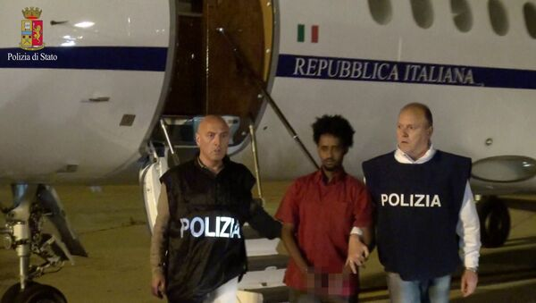 Medhanie Yehdego Mered (C), 35, is pictured with Italian policemen as they land at Palermo airport, Italy, following his arrest in Khartoum, Sudan, on May 24. - Sputnik International