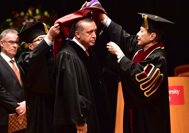 Turkish President Recep Tayyip Erdogan (C) wears an academic hood as he receives an honorary doctorate of laws from Waseda University president Kaoru Kamata (R) at the university in Tokyo on October 8, 2015