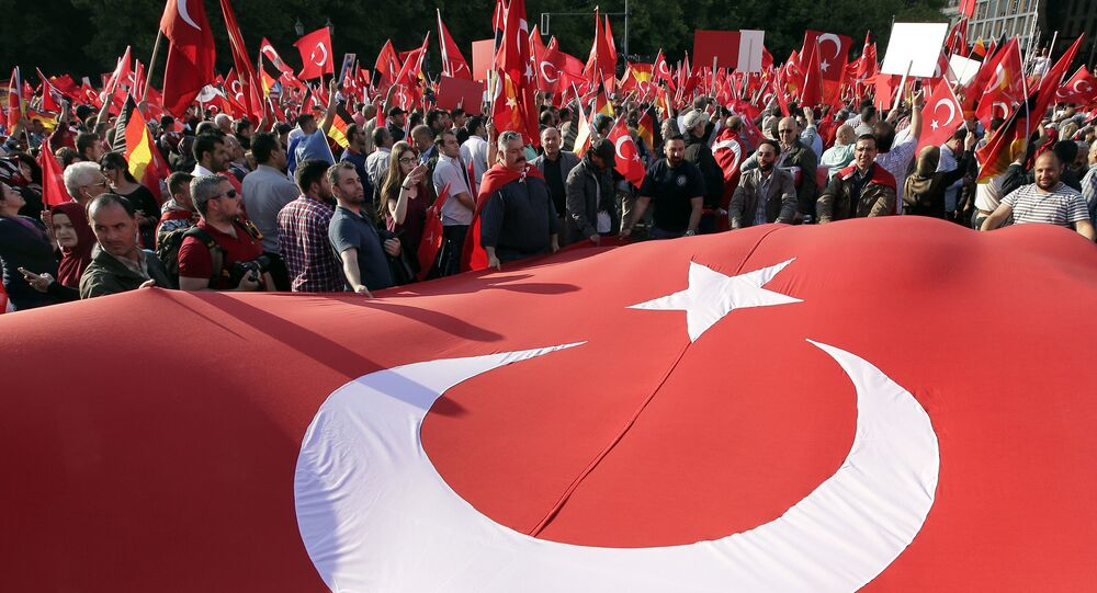 Protesters hold a national flag of Turkey in front of the Brandenburg gate in Berlin, Germany, Wednesday, June 1, 2016, as they demonstrate against a resolution of the German federal parliament, Bundestag, on the Armenian Genocide a century ago