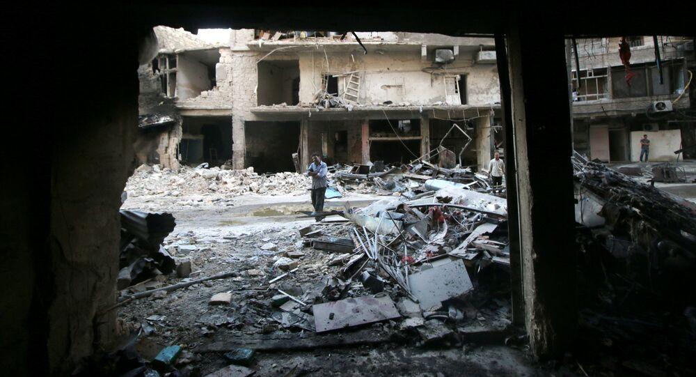 Men inspect damage after an air strike on Aleppo's rebel-held al-Shaar neighbourhood, Syria June 8, 2016