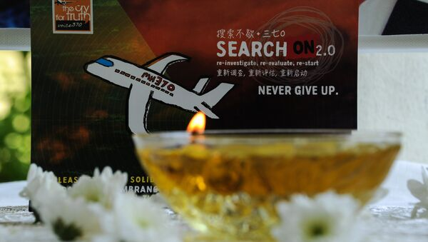 A candle burns a prayer message for passengers of missing Malaysia Airlines flight MH370 in Petaling Jaya on March 8, 2016 - Sputnik International