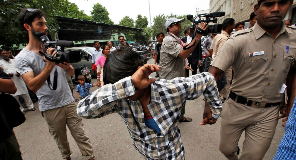 A man convicted for the gang rape of a Danish woman tries to hide his face as he is escorted by a policeman at a court in New Delhi, India, June 9, 2016