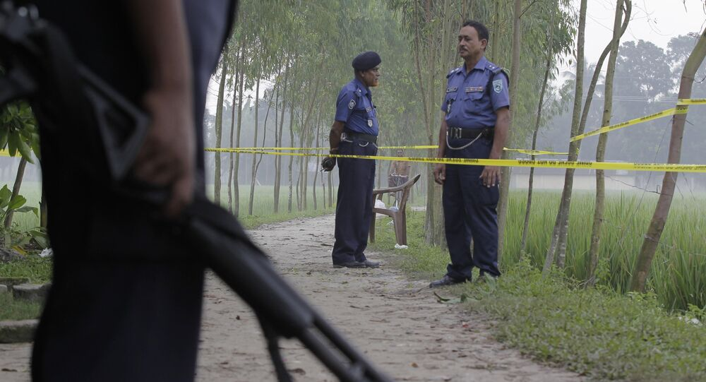 In this Oct. 4, 2015 file photo, Bangladeshi security officers stand by the site where Japanese citizen Kunio Hoshi was killed at Mahiganj village in Rangpur district, 300 kilometers (185 miles) north of Dhaka, Bangladesh