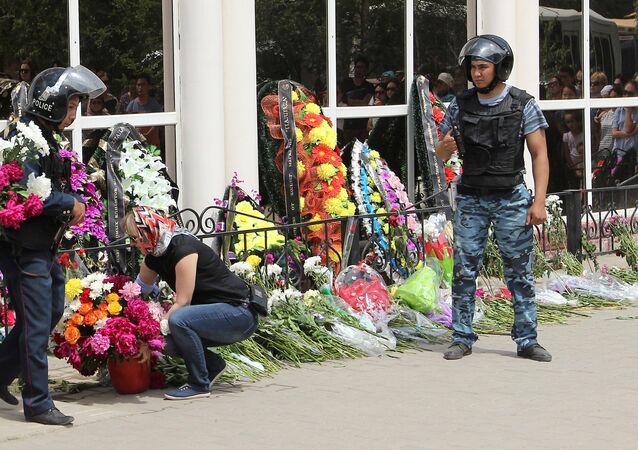 A woman places flowers as Interior Ministry members stand guard outside the firearms shop, which was a target of a recent suspected Islamist militant attack, during the funeral of salesman Andrey Maksimenko in Aktobe, Kazakhstan, June 8, 2016