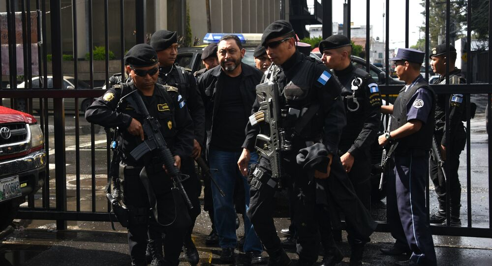 Former Guatemalan interior minister Mauricio Lopez (C) arrives at a courthouse after being arrested in Guatemala City on June 11, 2016